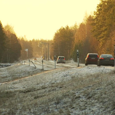 Tre bilar kör på en landsväg på vintern.