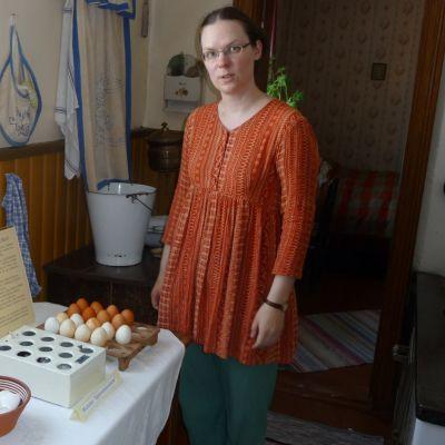 Nainen seisoo entisajan keittiössä