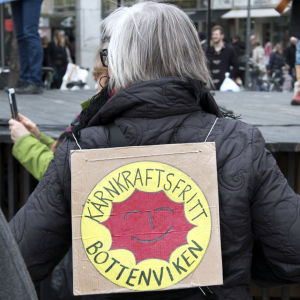 Demonstration mot kärnkraften i Umeå centrum, kvinna med skylt på ryggen