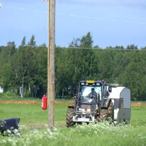 En traktor drar en husvagn på plats på Söderfjärden.