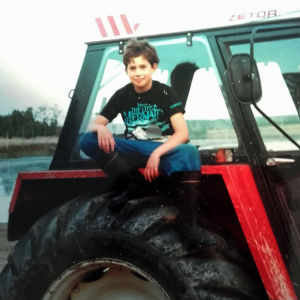 Nuori poika punaisen Zetor-traktorin päällä istumassa