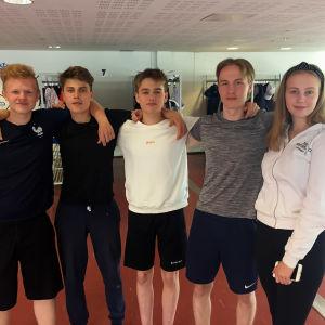 De fem ungdomarna står i bredd i skolans aula och håller armarna på varandas axlar.