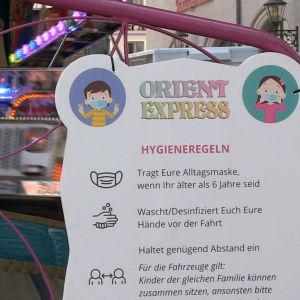 En skylt som visar de gällande coronareglerna om man vill åka karusell