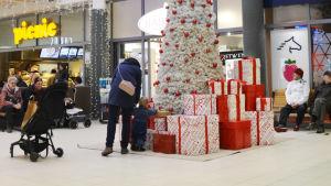 En stor vit julgran står mitt i Lundi köpcentrum. En mamma och ett litet barn har stannat för att titta på de stora julpaketen som ligger som prydnader invid granen.