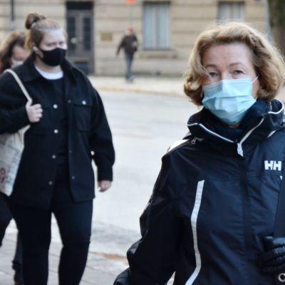En kvinna går på gatan med munskydd.