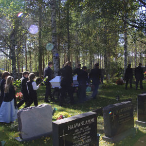 Hautajaissaattue kulkee kesäpäivänä koivujen keskellä hautausmaalla.
