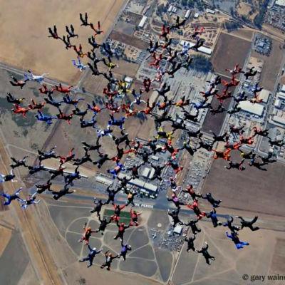 människor hoppar fallskärm i formation. Bilden tagen ovanom fallskärmshopparna.