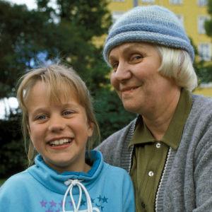 Sarjan Mummo Anna ja mummi lähikuvassa. Istuvat puistossa kesällä ja katsovat kameraan.
