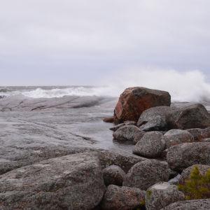 En strand med stora släta stenar. Stora vågor slår mot stenarna och himlen är grå.