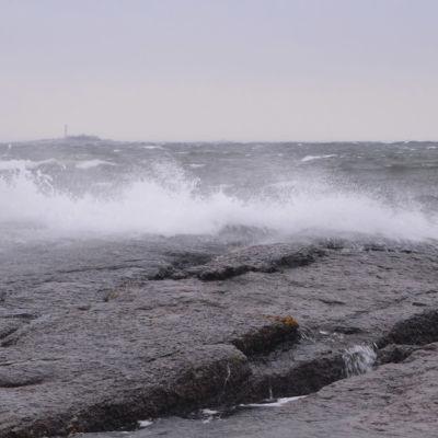 Meren aallot lyövät vaahdoten rantakallioon. Taivas on harmaa ja keli myrskyinen.