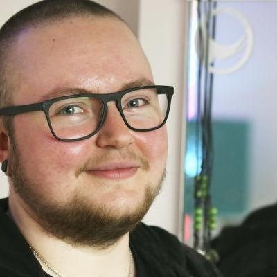 Kuvassa transmies Joonatan katsoo kameraan vähän vinottain ja hymyilee