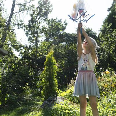 Pikkutyttö seisoo puutarhassa ja osoittaa sateenvarjolla kohti taivasta.