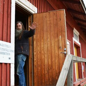 En man med långt hår står i dörröpningen till ett rött trähus. Han tittar ut och höjer handen till hälsning.