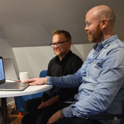 Två män sitter vid ett bord och tittar på en bärbar dator.