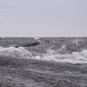 Stora vågor slår över en stenhäll.