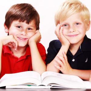 Kuvassa kaksi pikkupoikaa istuu pöydän takana ja hymyilee kameralla. Pöydällä on karttapallo ja koulutarvikkeita.
