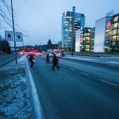 Ihmiset ylittävät tietä.