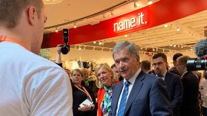 Till vänster syns en ung man som står bakom ett bord med läskedrycker på. Till höger synns president Sauli Niinistö..