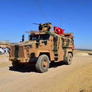 Panssaroitu miehistönkuljetusajoneuvo, jossa on Turkin lippu.