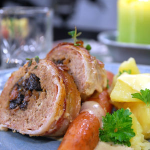En portion baconlindad köttfärslimpa med morot och potatis.
