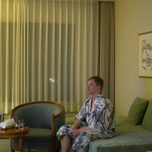 Kimonoon pukeutunut mies istuu sängyn reunalla hotellihuonessa ja tuijottaa eteenpäin.
