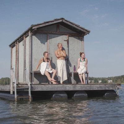 Tre personer insvepta i varsin handduk står på terrassen till en flytande, gråmålad bastu i en havsvik.