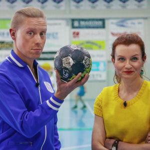 Nainen ja mies seisovat urheiluhallissa, mies pitää kädessään käsipalloa.