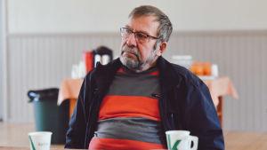 En äldre man med glasögon skägg sitter bakom ett långbord.
