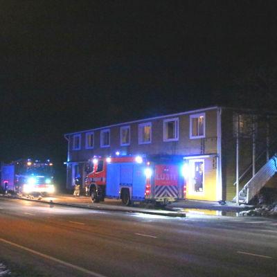 Två brandbilar utanför ett hus.