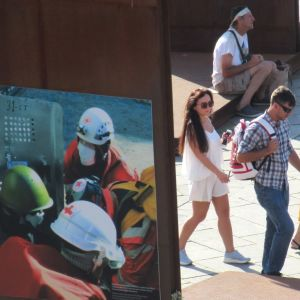 En kvinna med barnvagn, en man och en kvinna går förbi en plansch föreställande hjälparbetare. I centrum av Kiev är kriget närvarande bara på bilder.
