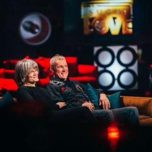 Pariskunta istuu sohvalla kuuntelemassa SuomiLOVE-esitystä