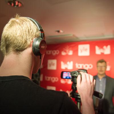 Kilpailija laulaa videokameralle tangomarkkinoiden esikarsintakiertueella Helsingissiä