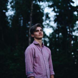 Porträttbild fotad lite underifrån av en ung man med mörkt hår och rosa skjorta.