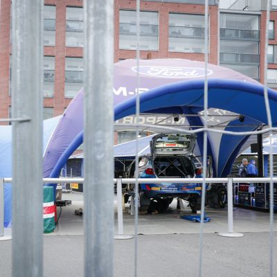 Ralliautoja Fordin teltoissa aidan takana Jyväskylän Lutakonaukiolla.