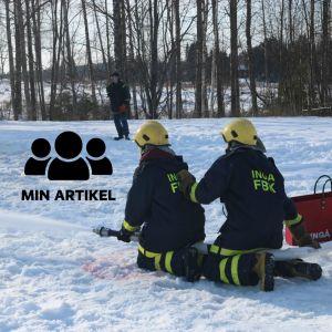 Två brandkårsklädda persone sprutar med en brandslang.