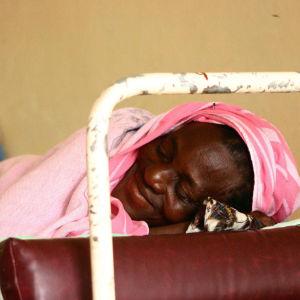 Kongolainen nainen makaa silmät kiinni hymyilevänä sairaalan rautasöängyssä.
