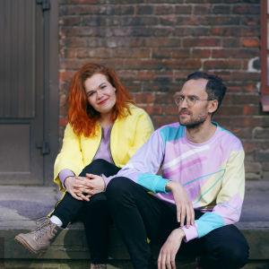 My och Axel befinner sig i en urban miljö, iklädda pastellfärgade kläder. My och Axel sitter på en sned lastbrygga. Bakom dem syns en tegelvägg.