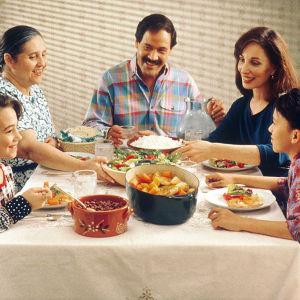 Familj som sitter runt ett bord och äter mat.