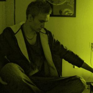 Thomas Nylund snurrar på en spak i ett gult sken.