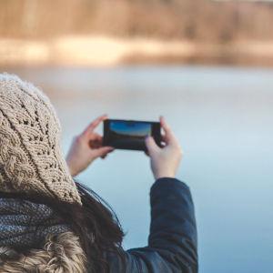 Tjej i vinterkläder som tar ett foto med en smarttelefon.