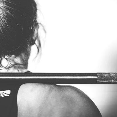 Kvinna, bakifrån, som lyfter en vikt i ett gym.