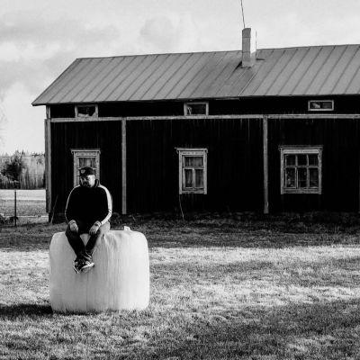 Joel sitter på en höbale framför ett torp. Bilden är svartvit.
