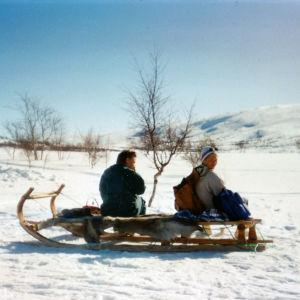 Tutkija Taina Kinnunen istuu ystävänsä kanssa vanhan mallisen kelkan päällä. Kuvattu Lapissa kevättalven aurinkoisena päivänä hankien hohtaessa valkoisena.