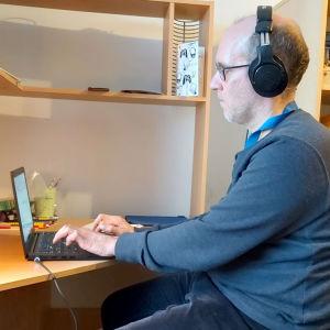 En man med hörlurar sitter framför en dator i ett hemmakontor.