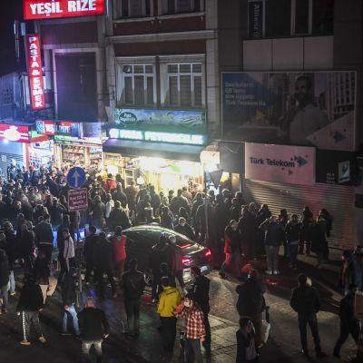 laaja väkijoukko Istanbulin kadulla liikkeiden edessä