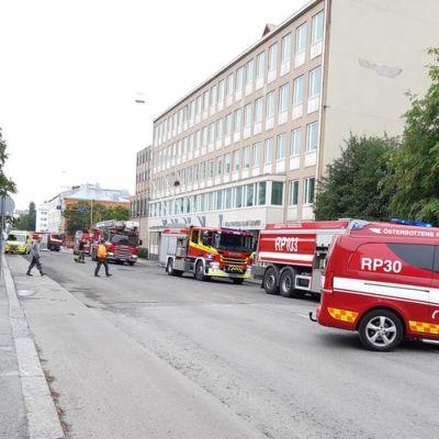 brandbilar utanför ett höghus.