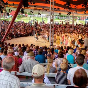 Publik runt en scen på vilken en stor barnkör uppträder.