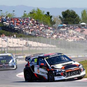 Rallycrossbilar kommer in i en kurva med hög fart.