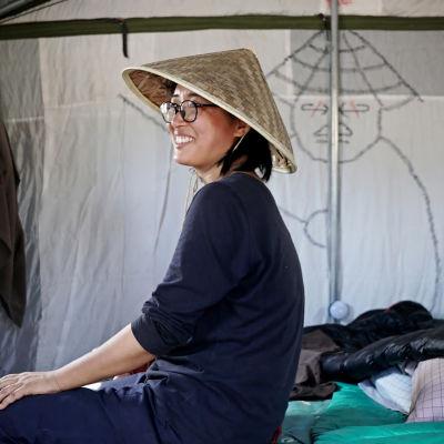 Another-yhteisössä asuva Jing Sun istuu sängyllään.