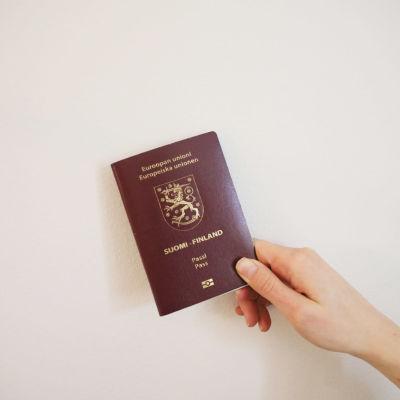 En hand håller i ett finskt pass mot en ljus vägg.